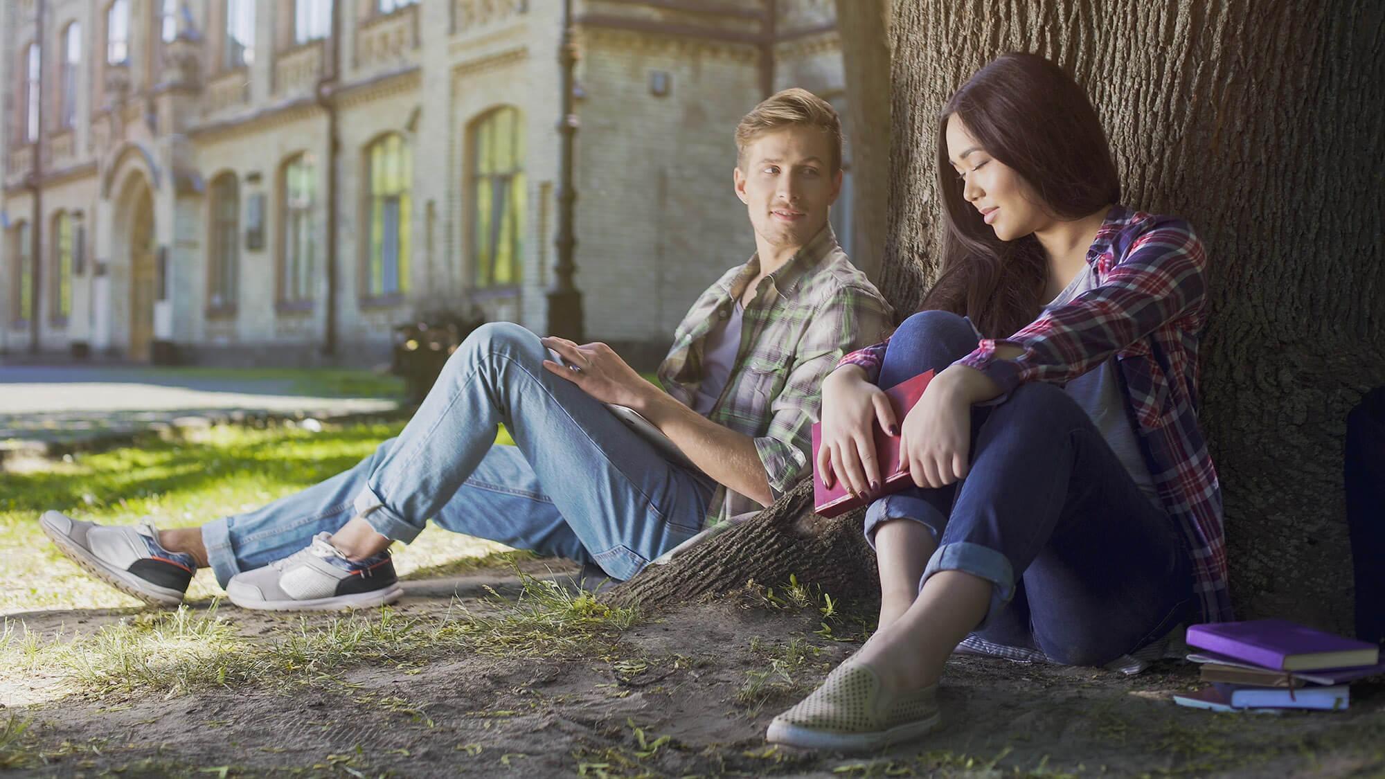 Mann sieht Frau unter einem Baum an