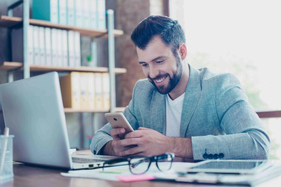 Mann lächelt im Büro auf sein Smartphone