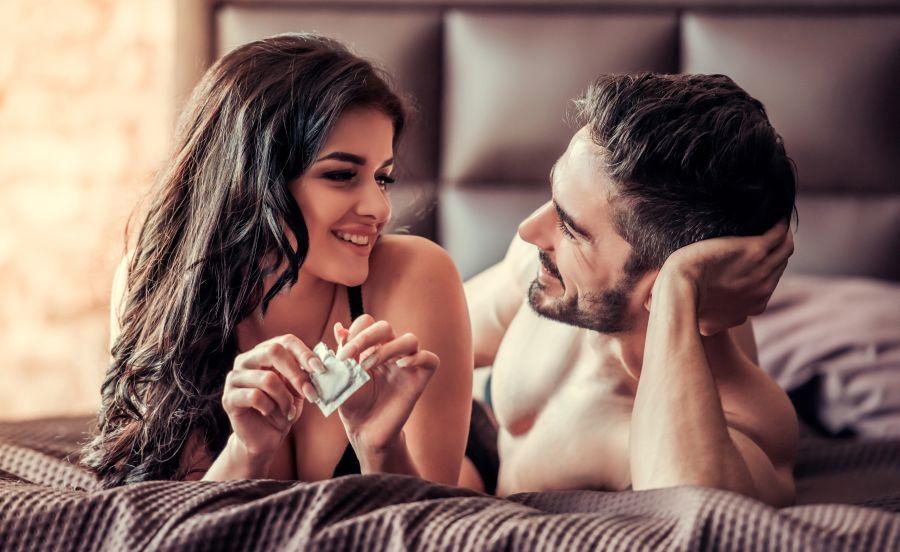 Paar im Bett mit Kondom